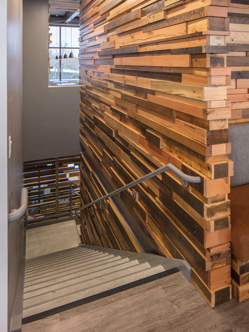 Reclaimed Wood Paneling on Walls along Workspace Stairs